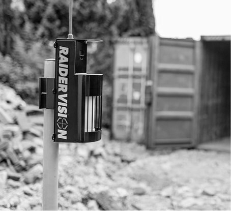 Black and white image of a RaiderVision security camera protecting a storage cabin
