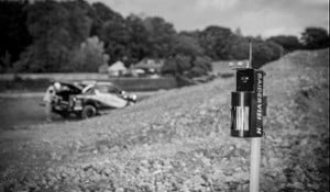A black and white image of a RaiderVision security system protecting a site with a car in the background